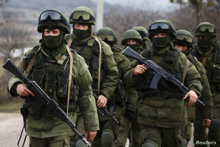Armed men, believed to be Russian servicemen, march outside an Ukrainian military base in the village of Perevalnoye near the Crimean city of Simferopol March 9, 2014. Shots were fired in Crimea to warn off an unarmed international team of monitors a...