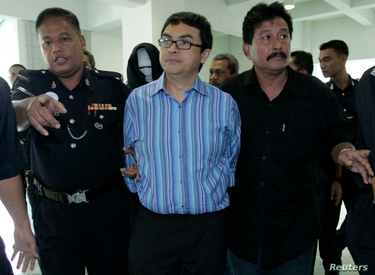 FILE - Abdul Razak Abdullah Baginda, center, is escorted by policemen as he leaves the courtroom in Shah Alam outside Kuala Lumpur, Sept. 3, 2007. Razak, 46, a close aide of Najib Razak, has been accused of involvement in the murder of 28-year-old Mo...