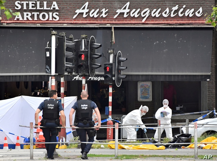 Forensic police, right, investigate at the scene of a shooting in Liege, Belgium, May 29, 2018.