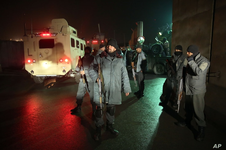Afghan police soldiers stand guard at the site of a suicide attack near a compound belonging to foreigners in Kabul, Afghanistan, Jan. 4, 2016.