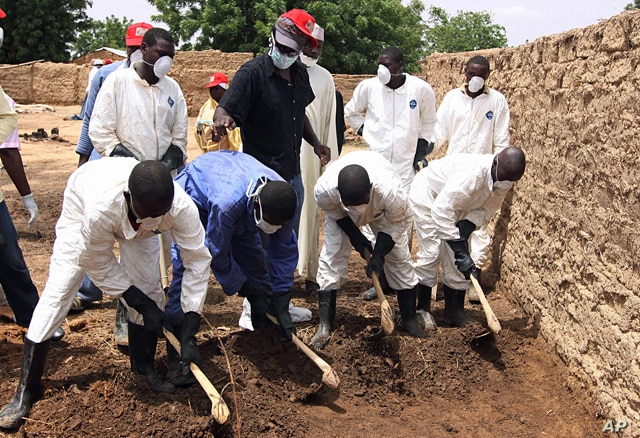 Health workers remove earth contaminated by lead from a family compound in the village of Dareta in Gusau, Nigeria, June 10, 2010.