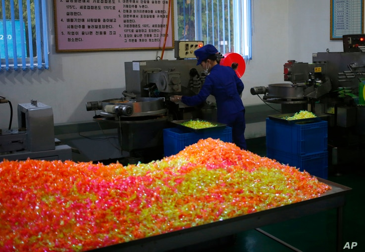 In this Oct. 22, 2018 photo, a worker monitors the production of sweets at Songdowon General Foodstuffs Factory in Wonsan, North Korea.
