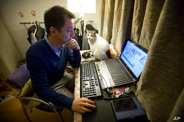 FILE -  Office worker Zhai, 28, who asked that only his last name be used, watches a live web stream from a Korean web performer on his computer at his apartment in Beijing.