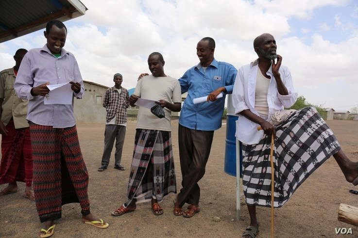 Somali Ahmed Omar Bihi and fellow refugees in Kakuma refugee camp check to see what names appear on a list for an interview with the International Organization for Migration (IOM) for potential U.S. resettlement. Kakuma, Kenya. February 6, 2017. (J. ...