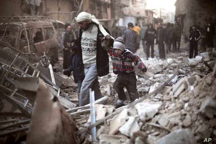 FILE - A man walks with a pair of children in hand through the rubble in Eastern Ghouta, Syria, Dec. 24, 2015. In one of the biggest incursions in years, warplanes are conducted dozens of airstrikes on rebel-held neighborhoods of the Syrian capital a...