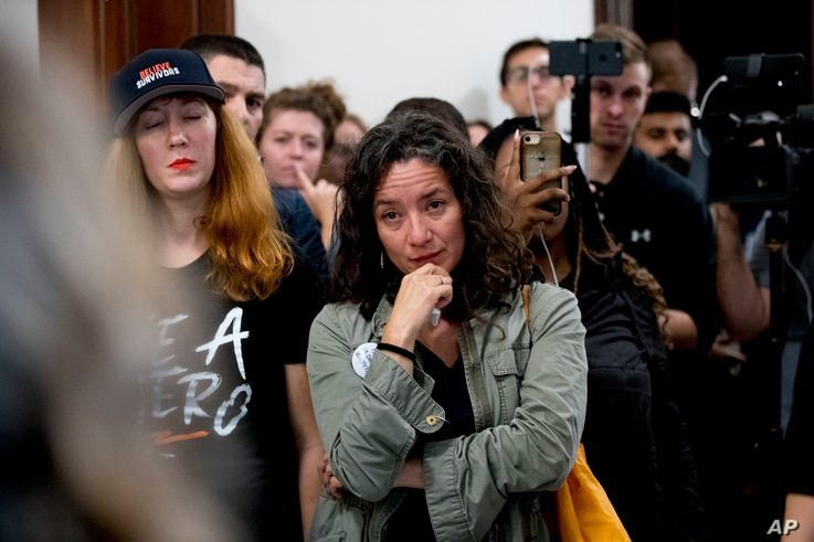 FILE - Ana Maria Archila of New York, N.Y., becomes emotional as protesters against Supreme Court nominee Brett Kavanaugh tell their personal stories of sexual assault outside offices of Sen. Jeff Flake, R-Ariz., on Capitol Hill, Sept. 24, 2018.