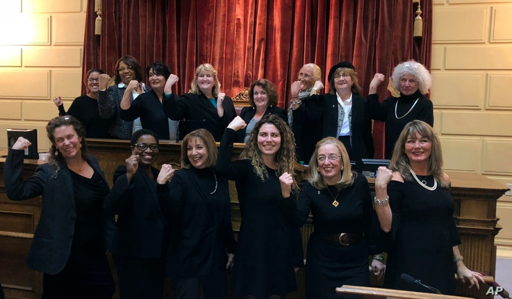 Rhode Island lawmakers wear black to in solidarity with the Time's Up movement and as a statement against sexual misconduct stand, at the House speaker's rostrum at the Statehouse in Providence, Rhode Island Jan. 9, 2018.