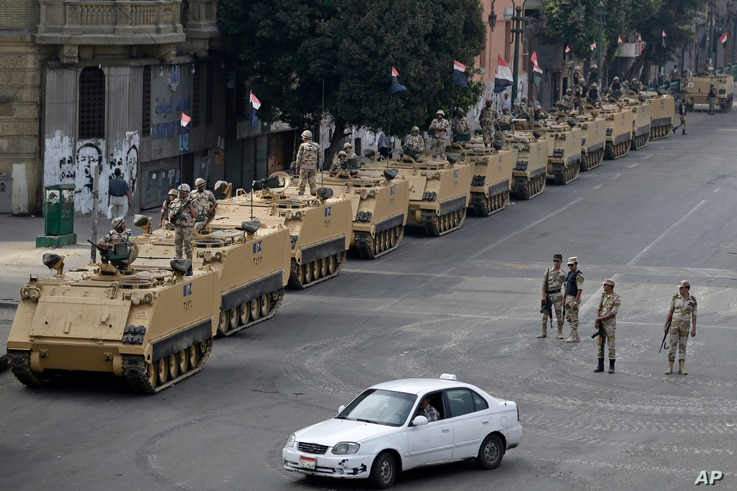 Egyptian army soldiers take their positions on top and next to their armored vehicles while guarding an entrance to Tahrir square, in Cairo, Egypt, Friday, Aug. 16, 2013.