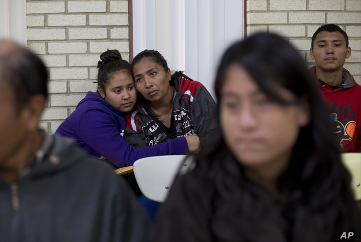 FILE - Central American migrants embrace as they wait for assistance at a center for newly-arrived migrant families with children, at Sacred Heart Catholic Church in McAllen, Texas. Assistance includes clothes, a meal, a shower and access to medical ...