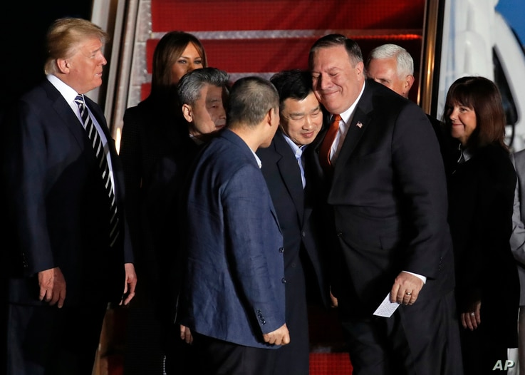 President Donald Trump, left, with first lady Melania Trump, watch Secretary of State Mike Pompeo, right, embrace former North Korean detainee Tony Kim, with Kim Hak Song, third from left, and Kim Dong Chul, front, upon their arrival, May 10, 2018, a...