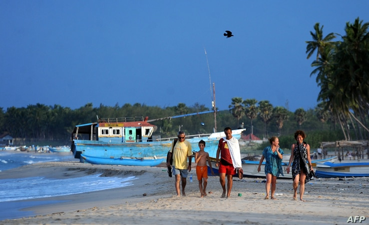 FILE - Foreign tourists walk along a beach in Sri Lanka's seafront eastern town of Trincomalee on July 7, 2010.