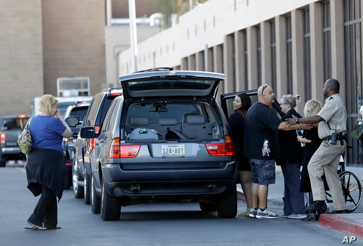 Shooting victim Taylor Stovall gets into a vehicle as her parents Wendy Stovall, far left, and Daniel Stovall, third from left, thank hospital staff University Medical Center in Las Vegas, Nev., on Oct. 3, 2017.