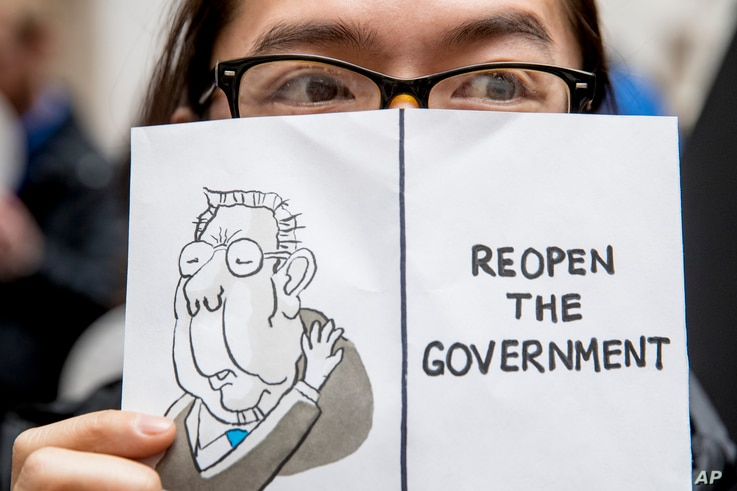 "A furloughed government worker affected by the shutdown holds a sign that reads ""Reopen the Government"" during a silent protest against the ongoing partial government shutdown on Capitol Hill in Washington, Jan. 23, 2019."
