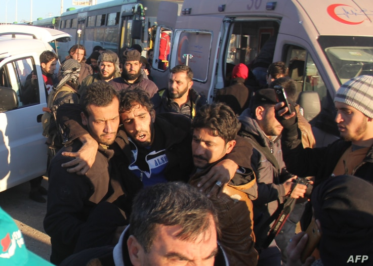 A wounded Syrian, who was evacuated from rebel-held neighborhoods in the embattled city of Aleppo, is carried upon his arrival in the opposition-controlled Khan al-Aassal region, west of the city, on Dec. 15, 2016.