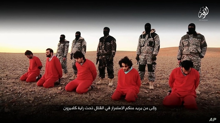 This undated image, taken from video posted online Jan. 3, 2016, by the communications arm of the Islamic State group, purports to show IS militants executing five men who they accuse of having spied for Britain in Syria.