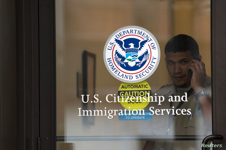 FILE - A security guard looks out of the U.S. Citizenship and Immigration Services offices in New York, Aug. 15, 2012.