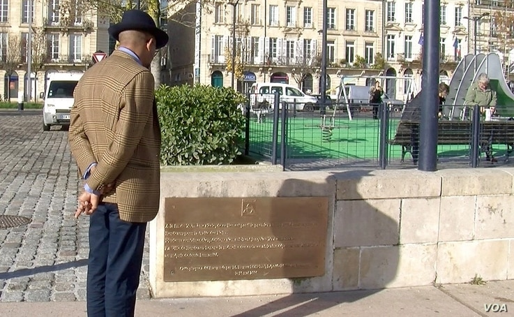 Karfa Diallo reads a plaque installed as a memorial to Bordeaux's slave-trading past. (L. Bryant/VOA)