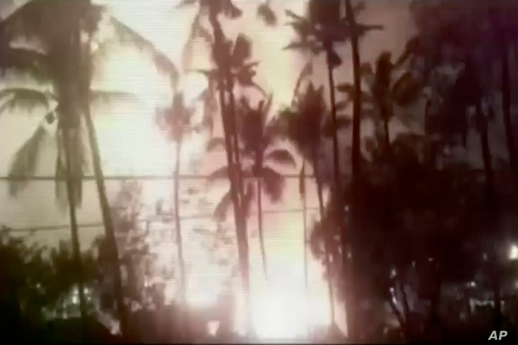 In an image from video, a flash from an explosion is seen from the ground during a fireworks show at a temple in Kollam, in the southern Indian state of Kerala, April 10, 2016.