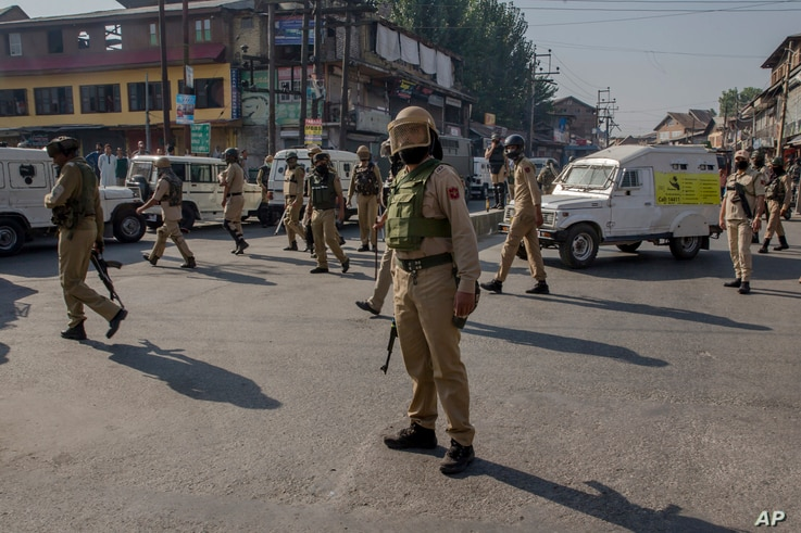 Indian police men watch as Kashmiri men carry the body of Mohammad Saleem Malik during his funeral procession in Srinagar, Indian controlled Kashmir, Sep. 27, 2018. Residents say government forces shot and killed the young man early Thursday during a...
