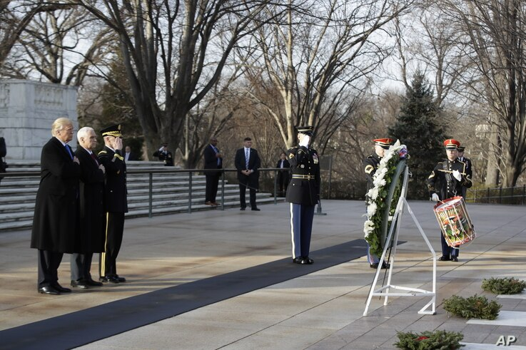 President-elect Donald Trump, accompanied by Vice President-elect Mike Pence pauses after placing a wreath at the Tomb of the Unknowns, Thursday, Jan. 19, 2017, at Arlington National Cemetery in Arlington, Va., ahead of Friday's presidential inaugura...
