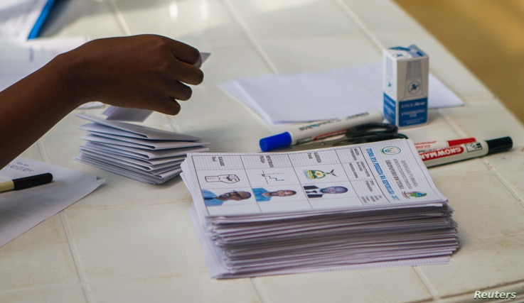 A polling assistant arranges ballot papers for voters to use at a polling station in Kigali, Rwanda, Aug. 4, 2017.