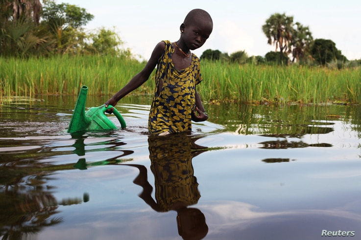 FILE - An internally displaced girl prepares to collect water in a plastic can in the Sudd Swamp near the town of Nyal, in South Sudan, Aug. 19, 2018.