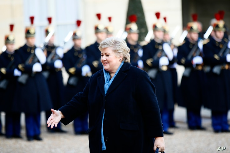 Norway Prime Minister Erna Solberg arrives to be welcomed by French President Emmanuel Macron before a global warming meeting at the Elysee Palace in Paris, Dec. 12, 2017.