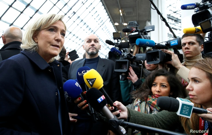 Marine Le Pen, candidate for the far-right French National Front, talks to journalists as she visits the Horse show in Villepinte, France, Dec. 2, 2016.