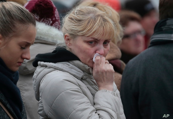 People react as they come to lay flowers in memory of the plane crash victims at Dvortsovaya (Palace) Square in St.Petersburg, Russia, on Wednesday, Nov. 4, 2015.