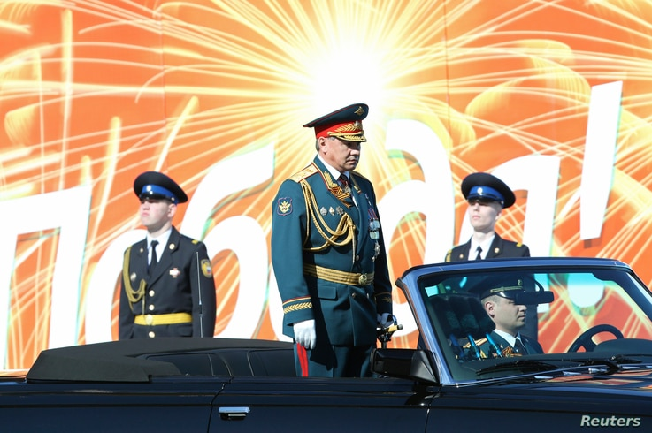 Russian Defence Minister Sergei Shoigu (C) reviews the troops during the Victory Day parade in Moscow's Red Square, May 9, 2014.