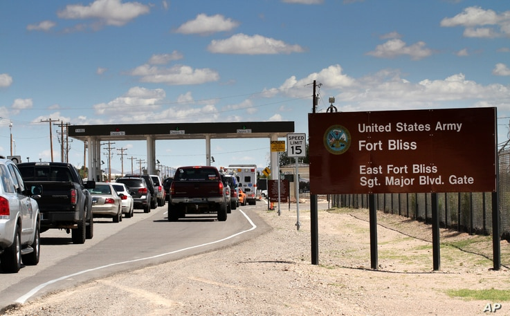 FILE -- Cars wait to enter Fort Bliss in El Paso, Texas.
