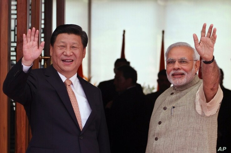 Indian Prime Minister Narendra Modi, right, and Chinese President Xi Jinping wave to the media as Modi welcomes Xi upon his arrival at a hotel in Ahmadabad, India, Sept. 17, 2014.
