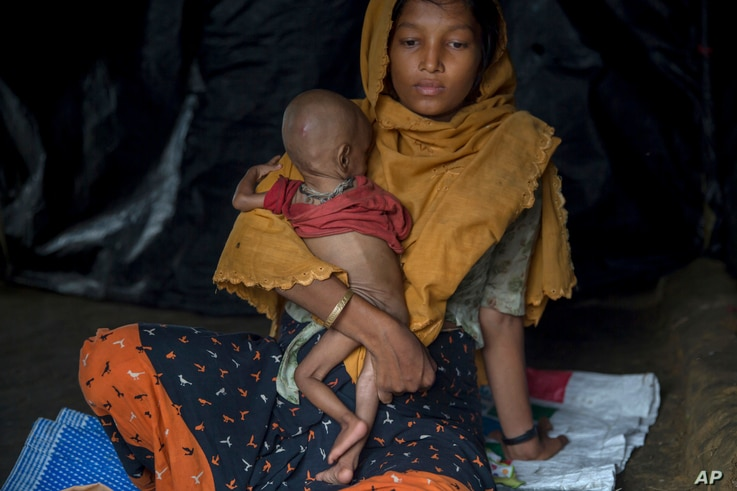 A Rohingya Muslim woman, who crossed over from Myanmar into Bangladesh, holds her 10-month-old son inside her shelter in Thaingkhali refugee camp, Bangladesh, Saturday, Oct. 21, 2017.
