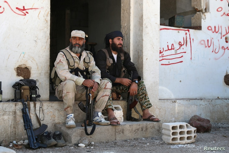 Rebel fighters rest with their weapons in Quneitra countryside, Syria Sept. 10, 2016.