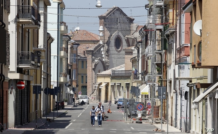 A semi-collapsed church is seen as people leave their homes in Mirandola, northern Italy, May 29, 2012.