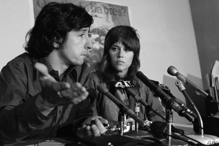 FILE - Tom Hayden talks as Jane Fonda listens at a news conference at the New York offices of the Center for Constitutional Rights, Jan. 2, 1973.