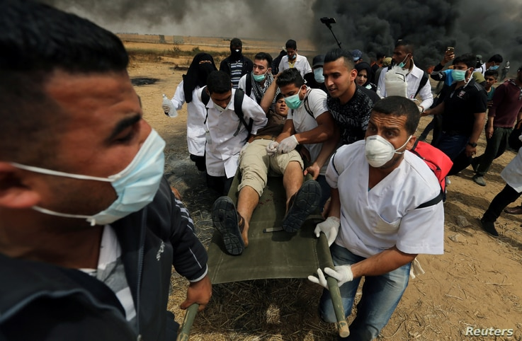 A wounded Palestinian is evacuated during clashes with Israeli troops at a protest where Palestinians demand the right to return to their homeland, at the Israel-Gaza border in the southern Gaza Strip, April 20, 2018.