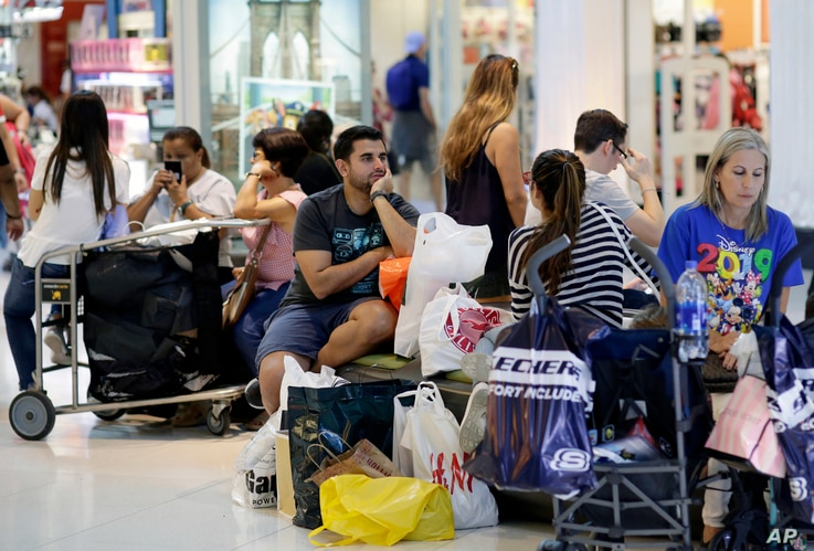 People take a break while shopping on Black Friday at Dolphin Mall, Nov. 23, 2018, in Miami.