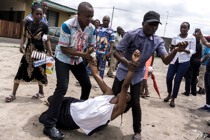A relative, carried by two men, reacts and mourns the death of a man who succumbed to a gun shot wound during a protest called on by the Catholic Church, to push for the President of the Democratic Republic of the Congo, to step down, Feb. 25, 2018 i...
