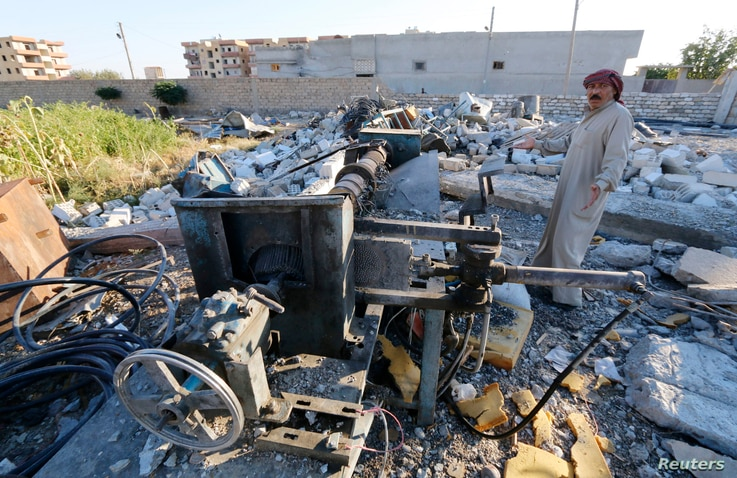 Abu Ismail, the owner of a plastics factory that was targeted by what activists said were U.S.-led air strikes, gestures while standing at his destroyed factory in the Islamic State's stronghold of Raqqa, Sept. 29, 2014.