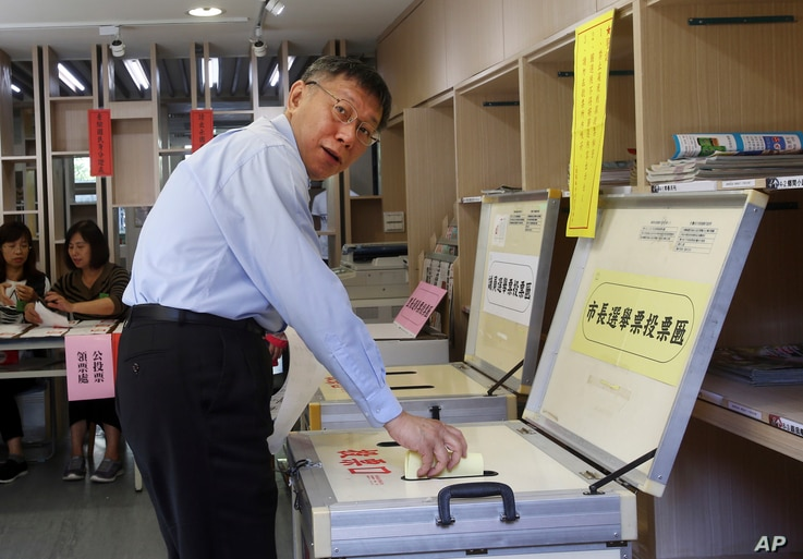 FILE - Taipei Mayor Ko Wen-je casts his ballot at a polling station, Nov. 24, 2018, in Taipei, Taiwan.