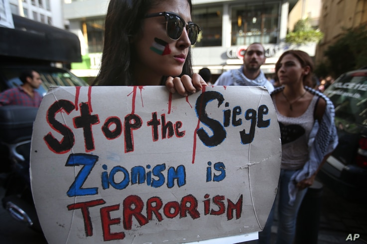 A Lebanese student from the American university in Beirut holds a placard during a protest against the Israeli offensive in Gaza, in Beirut, July 14, 2014.