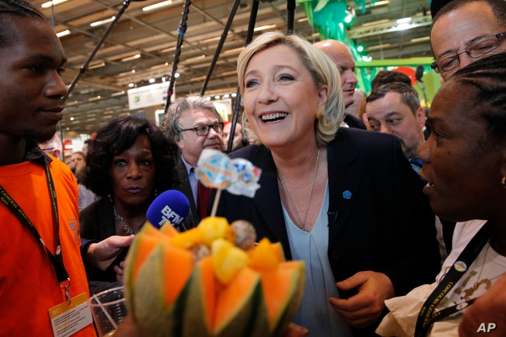 French far-right leader Marine le Pen smiles at the French Caraibean islands stand as she visits the Agriculture Fair Tuesday, Feb. 28, 2017 in Paris.
