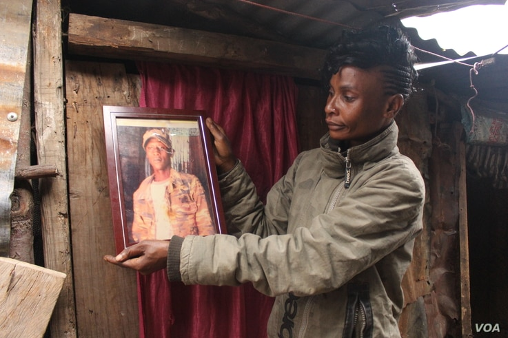 Mathare resident Sarah Wangari looks at photo of her son, gunned down by police in Kenya. (Photo: Rael Ombuor / VOA)