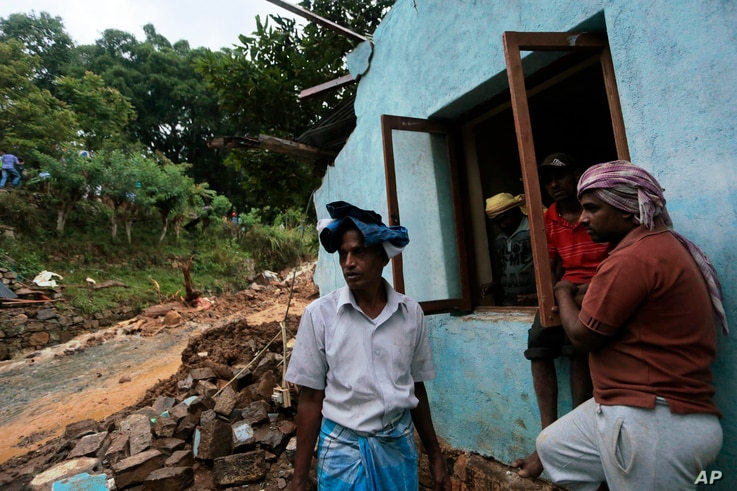 Sri Lankan men stand by their damaged house caused by mudslide at the Koslanda tea plantation in Badulla district, about 220 kilometers (140 miles) east of Colombo, Wednesday, Oct. 29, 2014. The mudslide triggered by monsoon rains buried scores of wo