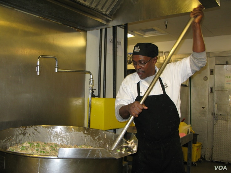 Production cook Gregory Jones uses a paddle to stir up turkey casserole at the DC Central Kitchen. (VOA/R. Skirble)