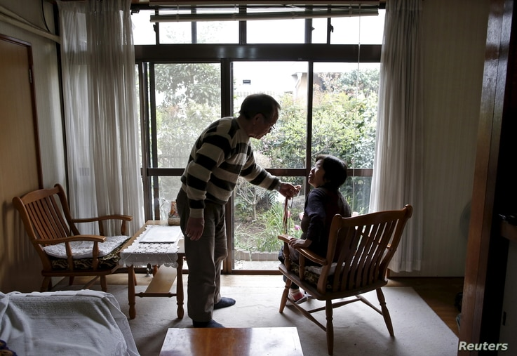 72-year-old Kanemasa Ito and his 68-year-old wife Kimiko, who was diagnosed with dementia 11 years ago, chat at their home in Kawasaki, south of Tokyo, Japan, April 6, 2016.