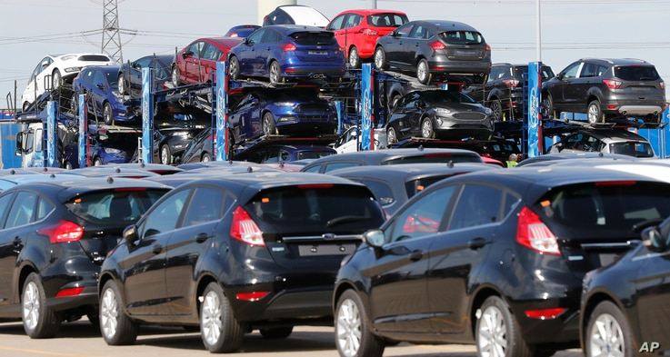 Ford cars wait for unloading after arrival by ship at the Ford Dagenham diesel engine plant in London, July 21, 2017. Ford joined other automakers Tuesday in offering incentives to car buyers who trade in older model cars.