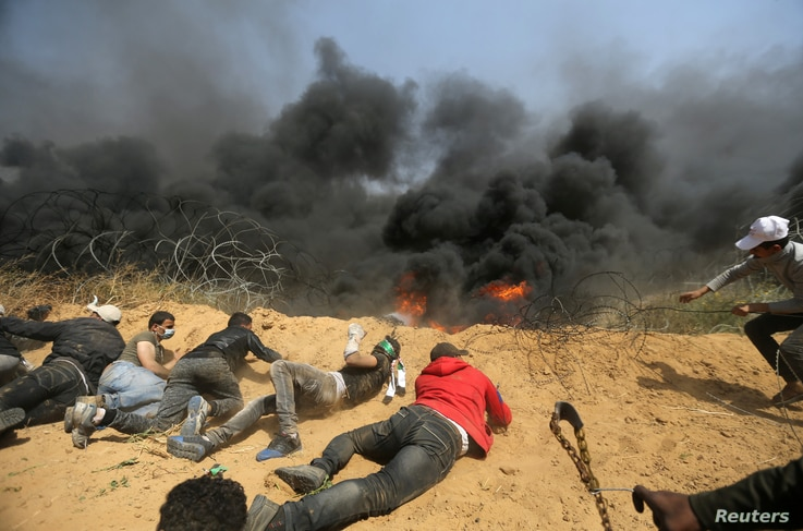 Palestinians remove part of the Israeli fence at the Israel-Gaza border during clashes at a protest demanding the right to return to their homeland, in the southern Gaza Strip, April 6, 2018.