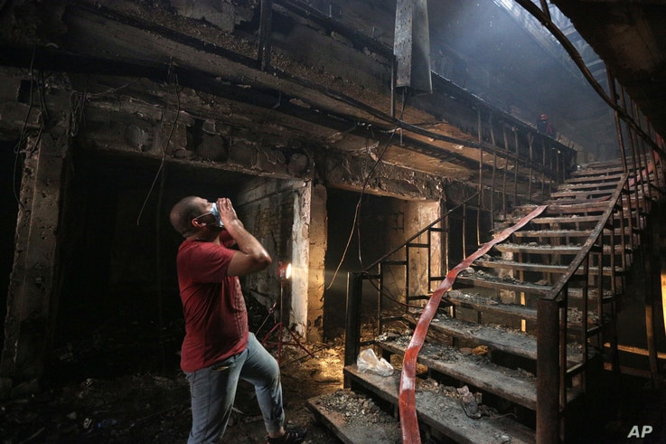 An Iraqi Man looks for victims at the site of a car bomb attack at a commercial area in Karada neighborhood, Baghdad, Iraq, July 3, 2016.